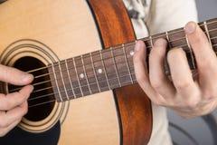 En bild av en akustisk gitarr, klassisk färg, i händerna av en gitarrist Fotografering för Bildbyråer