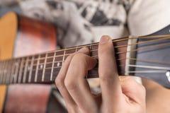 En bild av en akustisk gitarr, klassisk färg, i händerna av en gitarrist Royaltyfri Fotografi