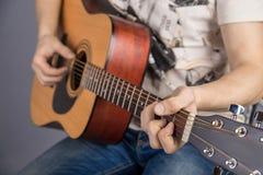 En bild av en akustisk gitarr, klassisk färg, i händerna av en gitarrist arkivbild