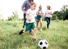 En bild av familjen som spelar fotboll tillsammans Pojken kör framme av alla Det finns manspring bak honom och Royaltyfri Fotografi