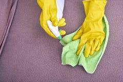 En bild av händer i gula handskar som gör ren soffan arkivbild