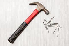 En bild av hammaren och spikar på trätabellen arkivbilder