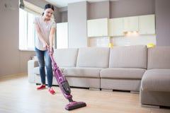 En bild av kvinnan står, i studiolägenhet och att göra ren golvet Hon använder dammsugare för det se för flicka royaltyfria bilder