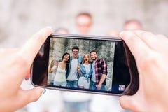 En bild av mänsklig ` s räcker innehavtelefonen Denna människa tar bilden av fyra lyckliga personer De står på grå färger Royaltyfri Foto