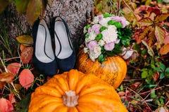 En bild av pumpor och bröllopbuketten som ligger nära brud- skor bröllop för band för inbjudan för blomma för elegans för bakgrun Arkivfoto