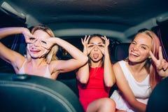 En bild av roliga flickor som gör roliga diagram runt om deras ögon De visar uo deras tungor Ett av dem är Arkivfoto