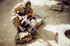 En bild av soldatsammanträde på jordningen och den bärande framsidamaskeringen Han rymmer det svarta geväret i händer Mannen ser Royaltyfri Bild