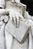 En bild av en staty med en bok i hans hand Royaltyfri Foto