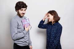 En bild av två riktiga vänner En stilfull grabb som går att framlägga hans vän med en gåva En lycklig ung kvinna som går att mott arkivfoton