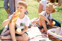 En bild av ungar som sitter på gräs och äter mat Flickan äter ett äpple, medan pojken är stickande bröd Deras föräldrar är Royaltyfri Fotografi