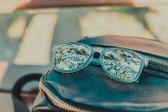 En bild med stilfull solglasögon nära en ryggsäckpåse arkivfoton