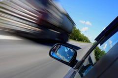 En bilkörning på en väg på höga hastigheter royaltyfria foton