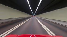 En bilkörning på en gata på höga hastigheter som passerar andra bilar arkivbild