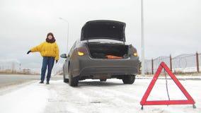 En bilolycka Ett anseende för ung kvinna vid en bruten bil Fånga en bil för hjälp Ett nöd- tecken arkivfoto