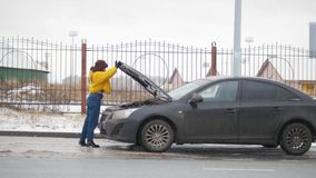 En bilolycka Ett anseende för ung kvinna vid en bruten bil och öppnar en bilhuv arkivfoton