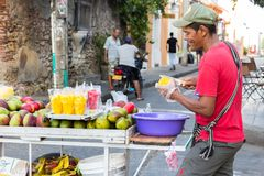 En bitande mango för fruktförsäljare i Cartagena royaltyfri foto
