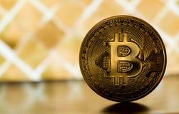 En bitcoin på guld- backround Arkivbild