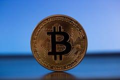 En bitcoin på guld- backround Arkivfoto