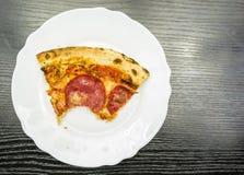En biten del av peperonipizza på en platta ovanför sikt royaltyfri bild