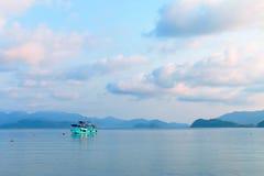 En blå fartygflöte i havet av golfen av Thailand som omgav vid berg Arkivbild