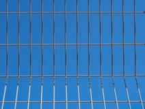 En blå himmel till och med ett metallgaller Arkivfoto
