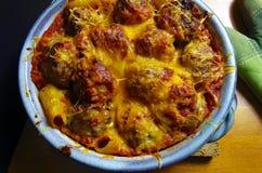 En blå keramisk eldfast form som fylldes med ost, täckte köttbullar och pasta Arkivbilder