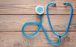 En blå stetoskop på en trätabell Medicinsk kardiologiutrustning Top beskådar Arkivfoto