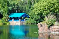 En blå trästruktur nära ett damm och gräsplanträd Royaltyfri Fotografi