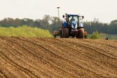En blå traktor med en kärna ur borrar in ett plöjt fält arkivfoton