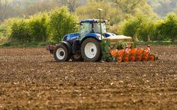 En blå traktor med en kärna ur borrar in ett plöjt fält Royaltyfria Foton