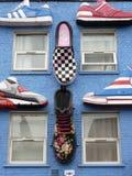 En blå vägg med påfyllningar av skor royaltyfri bild