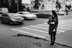 En blått för tonårs- flicka täcker anseende på trafikljuset på stadsgatan på cloudly en höstdag med att förbigå för medel Royaltyfri Foto