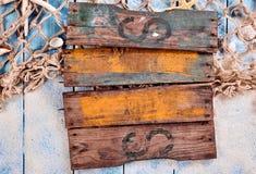 En blanco de madera viejos firman encima la arena y la red de pesca Fotos de archivo