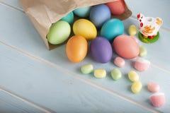 En blandning av färgrika fega ägg för feriepåsk i en påse och sötsaker för pappers- hantverk arkivbilder