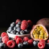 En blandning av hallonet och blåbäret med en passionfruit, på mörka lodisar Royaltyfri Fotografi