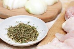 En blandning av kryddor i förgrunden och en höna och en huggen av lök på träbräde på tabellen Arkivbild