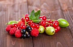 En blandning av mogna bär på en trätabell för livstid sommar fortfarande Hallon krusbär, vinbärnärbild Royaltyfri Bild