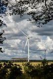 En blick till vindgeneratorn på fältet till och med träd Royaltyfria Foton