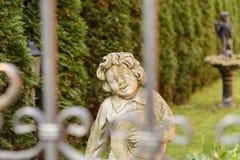 En blithesome staty av en pojke i trädgården Arkivfoto