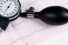 En blodtryckmanometer på en kardiogram ECG, aneroid- sphygmomanometer Medicinsk sjukvård Fotografering för Bildbyråer
