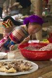 En blommahmong och hon behandla som ett barn att äta på den Bac Ha Week slutmarknaden Arkivbild