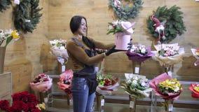 En blomsterhandlaresäljare i shoppar händer en bukett av blommor till en köpare lager videofilmer