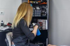 En blond flicka för tattooist söker efter ett hjälpmedel för att starta hennes arbete Royaltyfri Foto