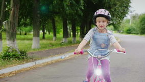 En blond flicka i en hjälm som rider en cykel på gatan Carefree barndom steadicamskott arkivfilmer