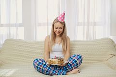 En blond flicka i ett pajamalock med en kaka med en stearinljuscelebrat arkivfoton