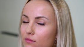 En blond flicka med bruna ögon i studio som tittar seriöst på kameran stock video