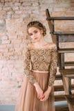 En blond flicka poserar i en mjuk sandig brun klänning med en snöra åtöverkant och med en tyllkjol Bilden av partiet _ arkivfoton