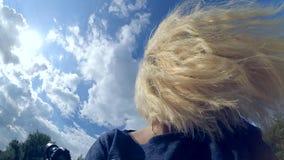 En blond flicka sitter med ett vippat på huvud lager videofilmer