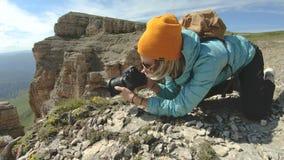 En blond flickafotograf i en hatt tar en bild i ett konstigt poserar på hennes digitala kamera med en bakgrund av vaggar in arkivfilmer