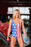 En blond flickakroppsbyggare i en sportig mångfärgad body svänger med en hantel inom arkivbild